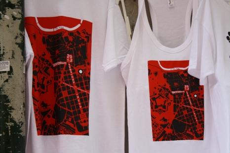 Las camisetas con el póster de este año, un mapa de la ciudad con forma de toro.