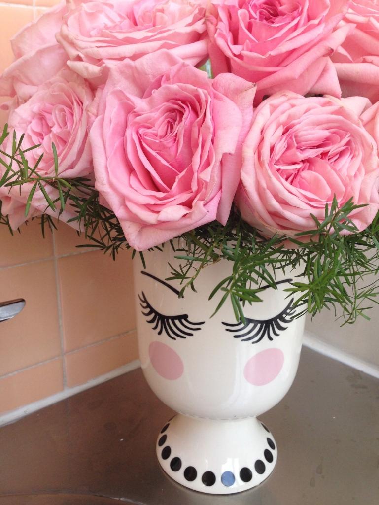 Las rosas rosas, el follaje verde y el hermoso florero con un toque hiper fermenino y vintage combinaba perferctamente con las paredes y pisos de cerámica del baño de damas.